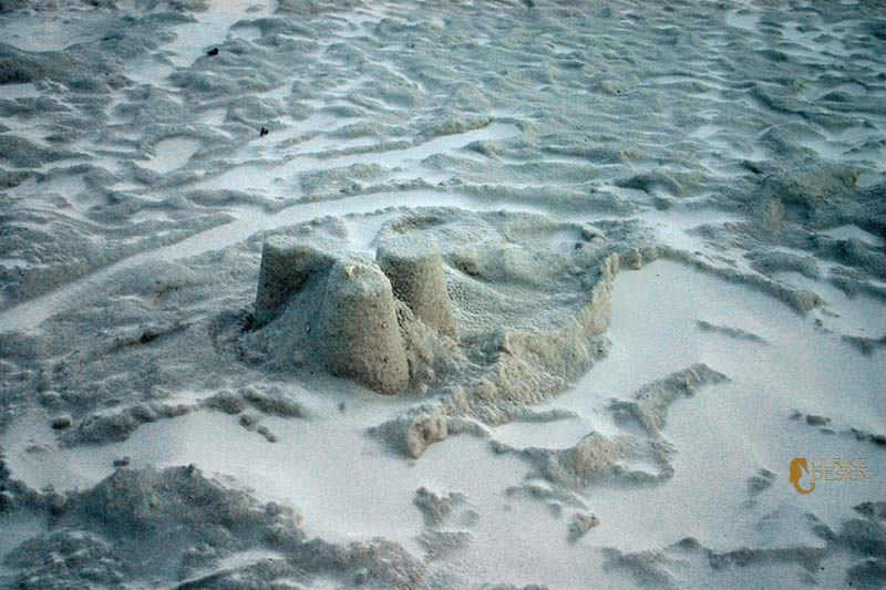A ruin of a sandcastle with a dusting of powdered sand.